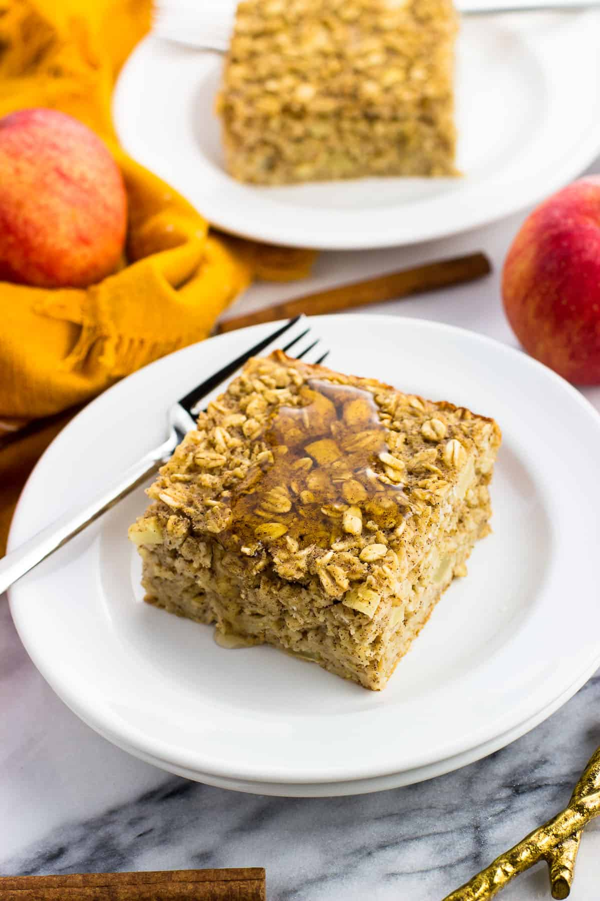 A piece of apple baked oatmeal on a plate with a fork next to a linen napkin, apples, and a cinnamon stick.