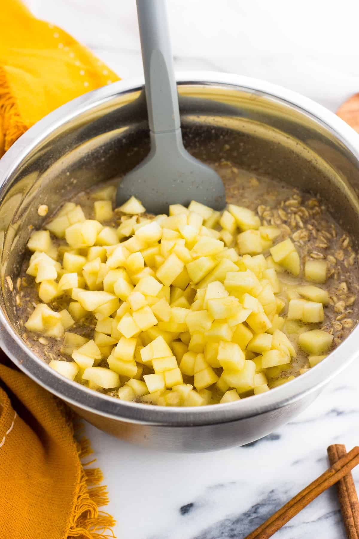 The baked oatmeal mixture in a metal mixing bowl with a spatula with the chopped apples poured on top.