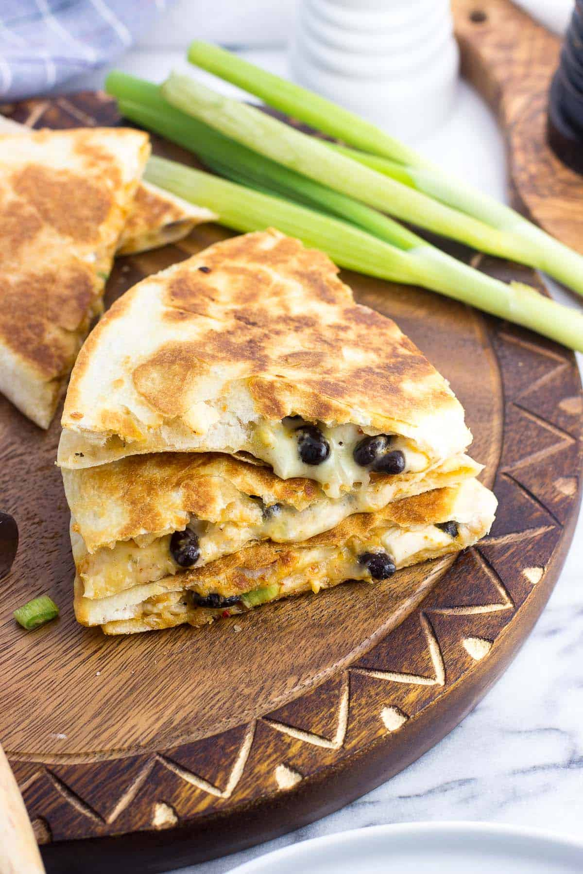 A stack of three quesadilla wedges on a wooden board with a bunch of green onions in the background