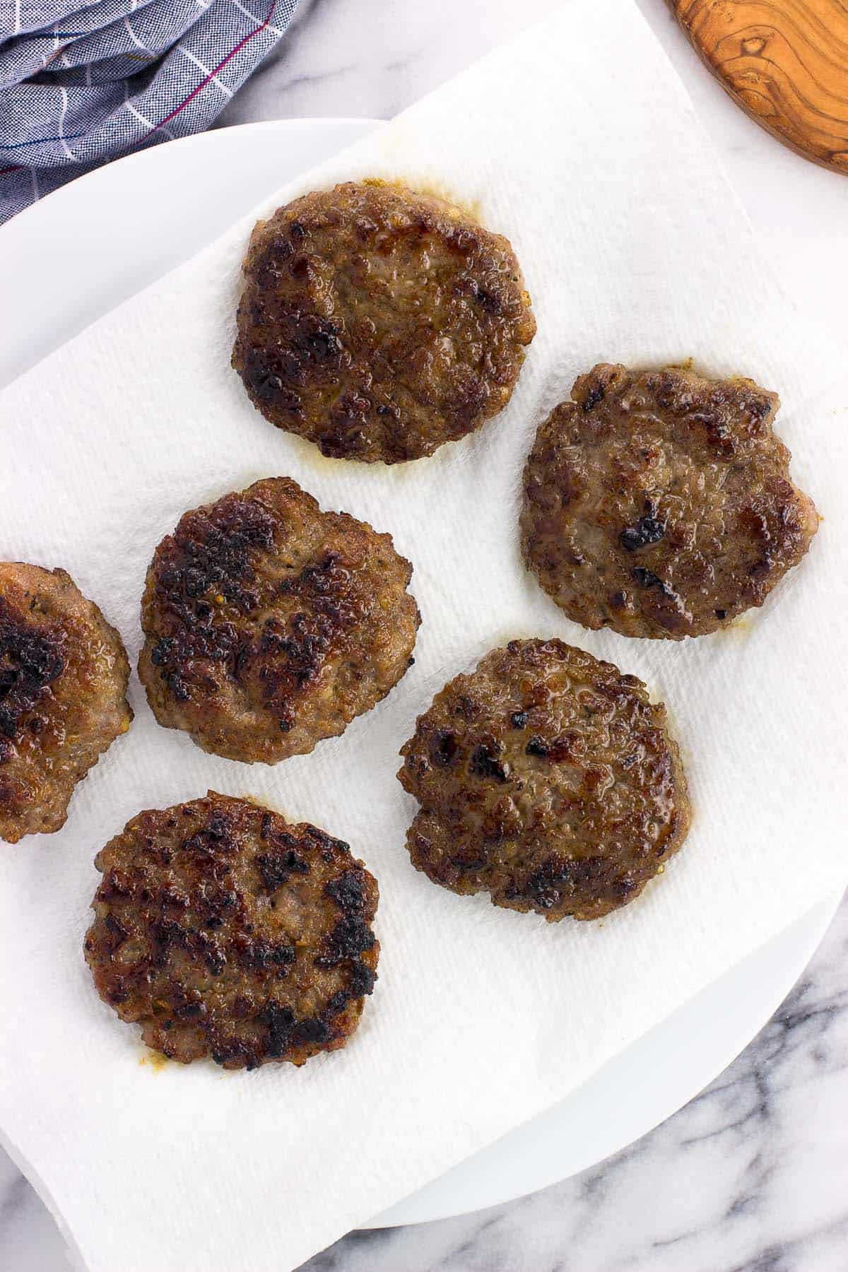 Cooked sausage patties draining on a paper-towel lined plate
