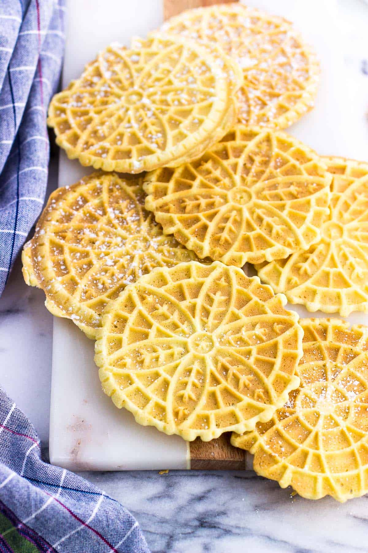 A pile of pizzelle cookies on a marble board