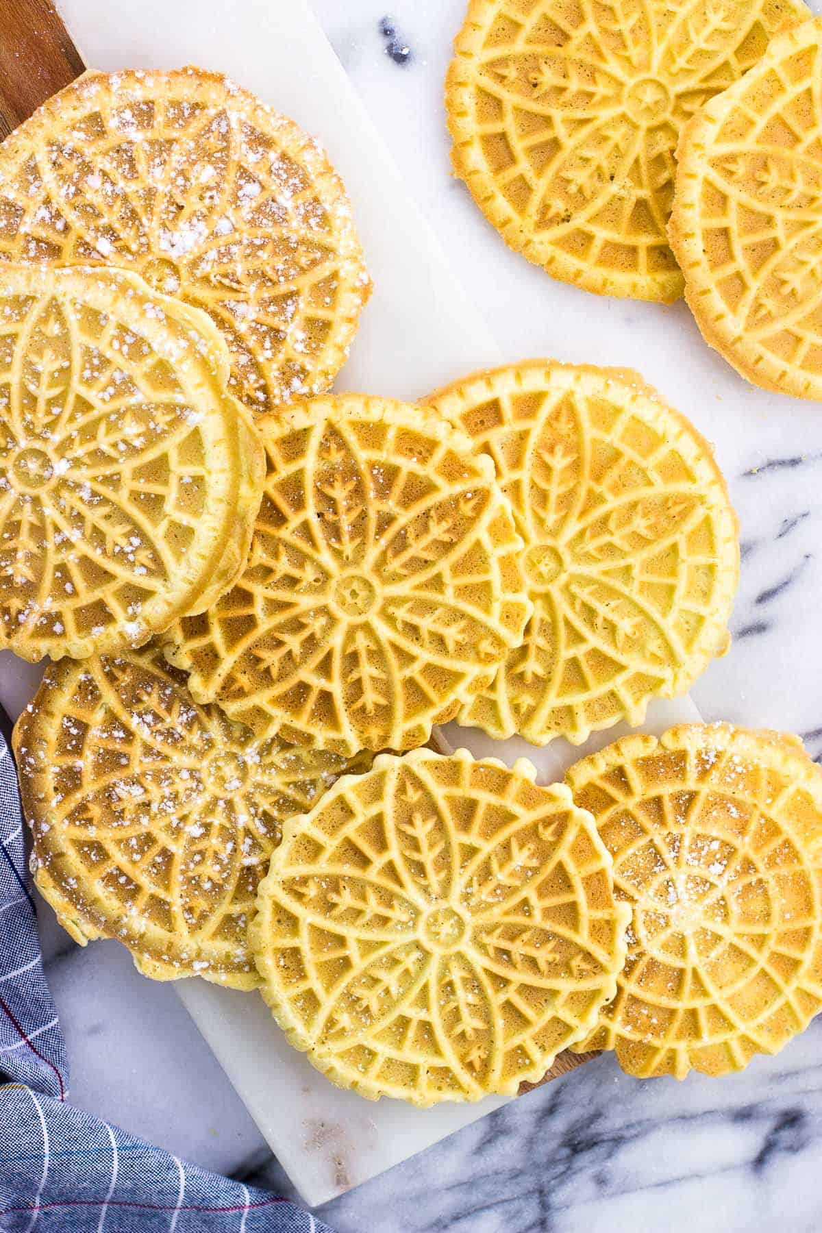 Pizzelle dusted with powdered sugar on a marble board