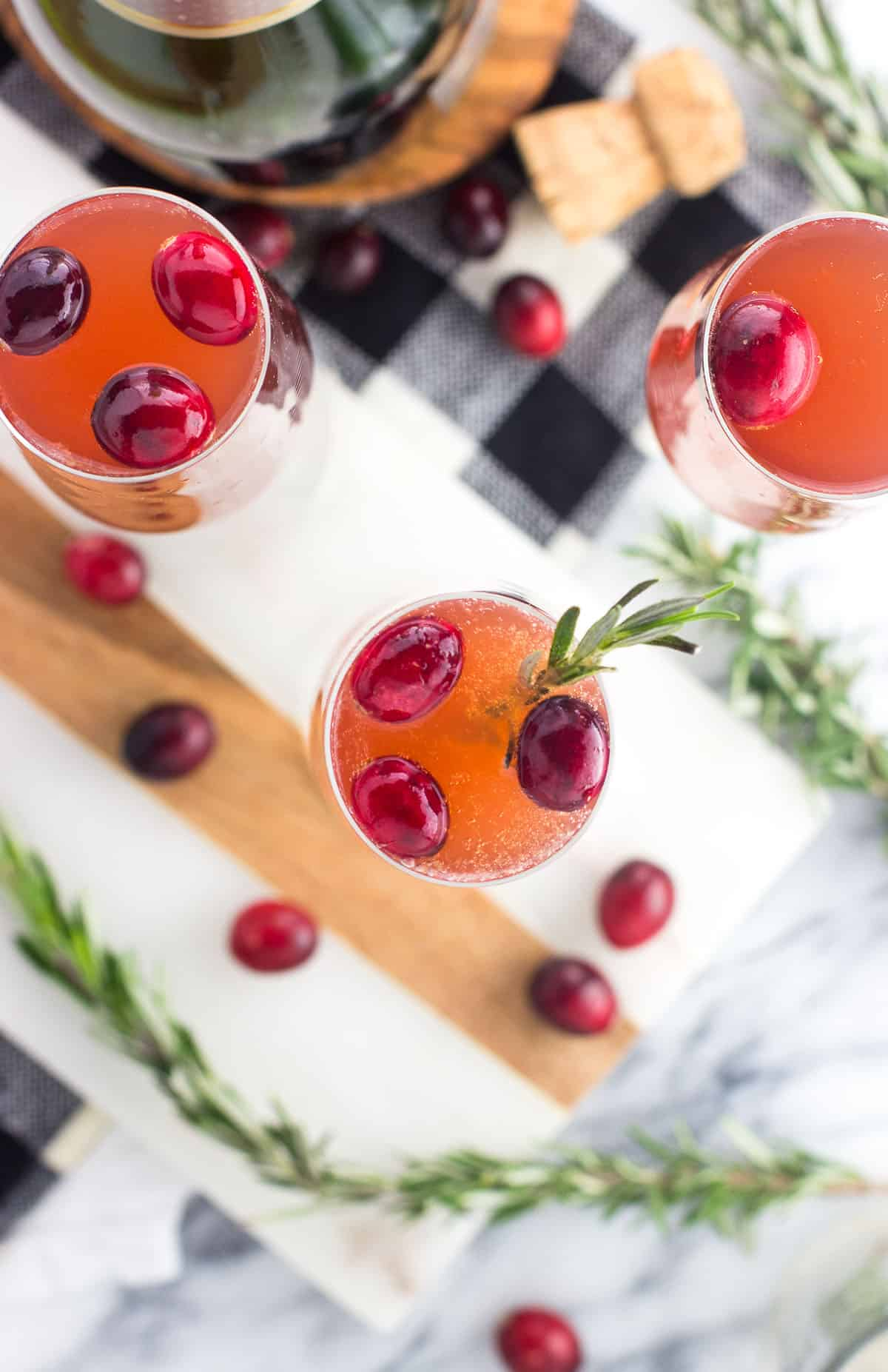 An overhead picture of mimosas in flutes garnished with fresh cranberries and rosemary sprigs