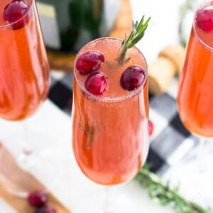 A cranberry mimosa in a champagne flute garnished with cranberries and fresh rosemary