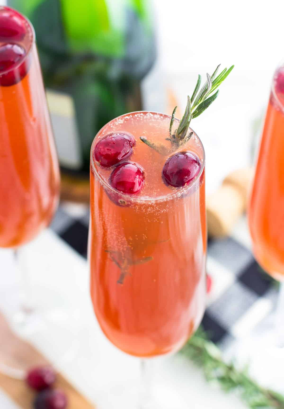 A close-up of a cranberry mimosa with three fresh cranberries and a sprig of rosemary for garnish