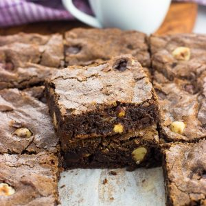 A pan of chocolate hazelnut brownies cut into squares with two brownies stacked on top of one another