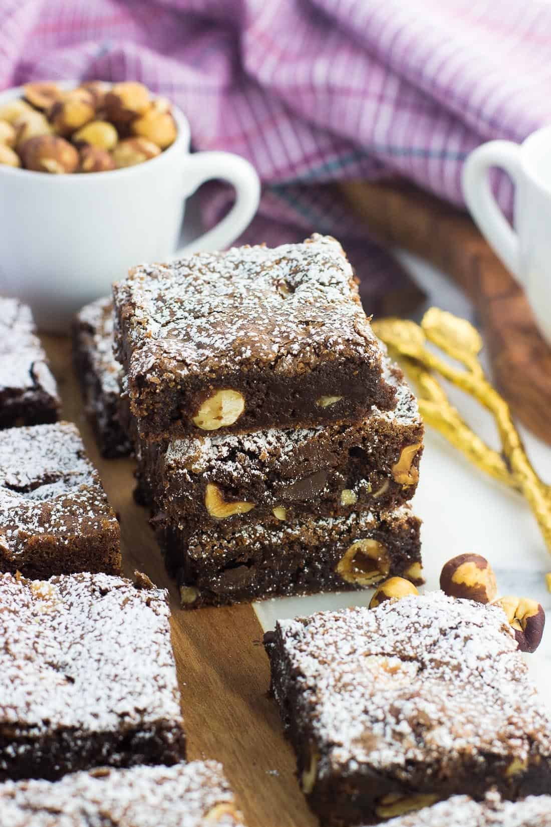 A stack of three hazelnut brownies dusted with powdered sugar