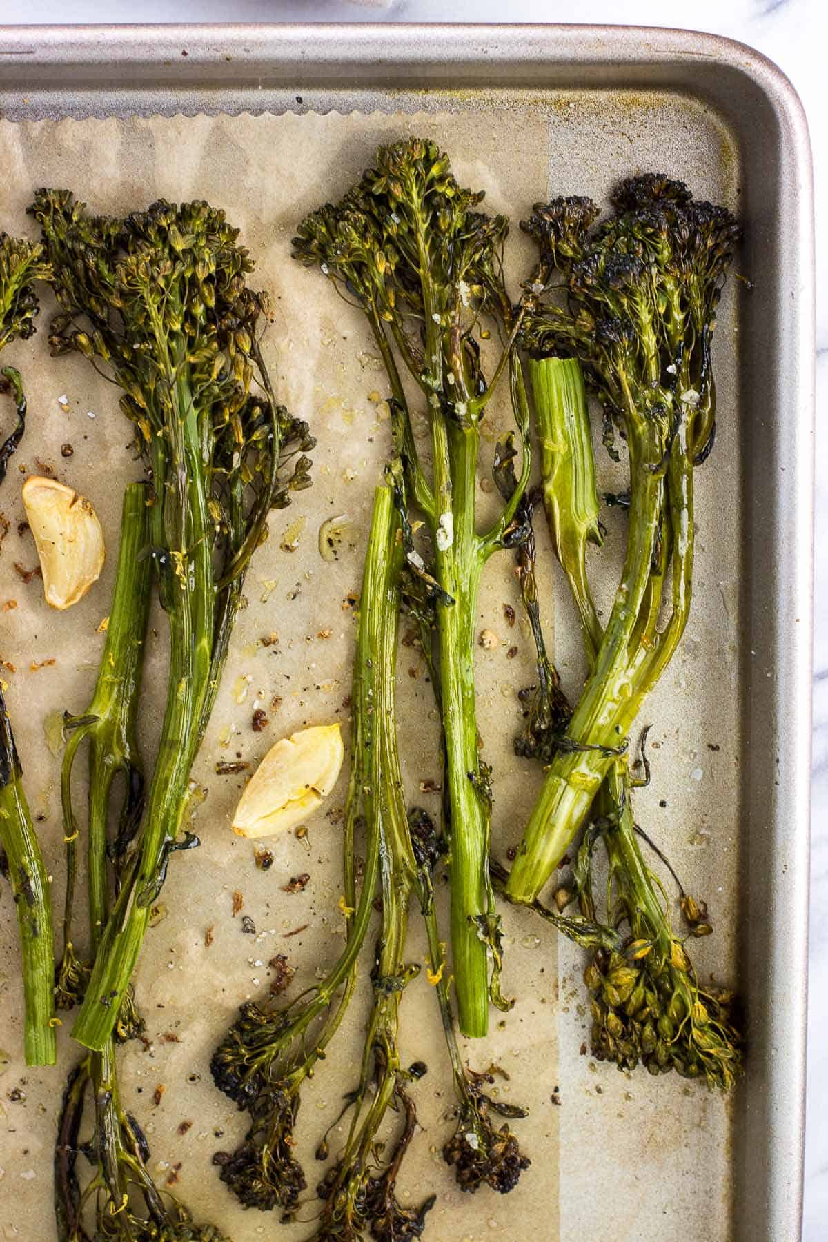 An overhead view of roasted broccolini spears and garlic cloves on a parchment-lined baking sheet.
