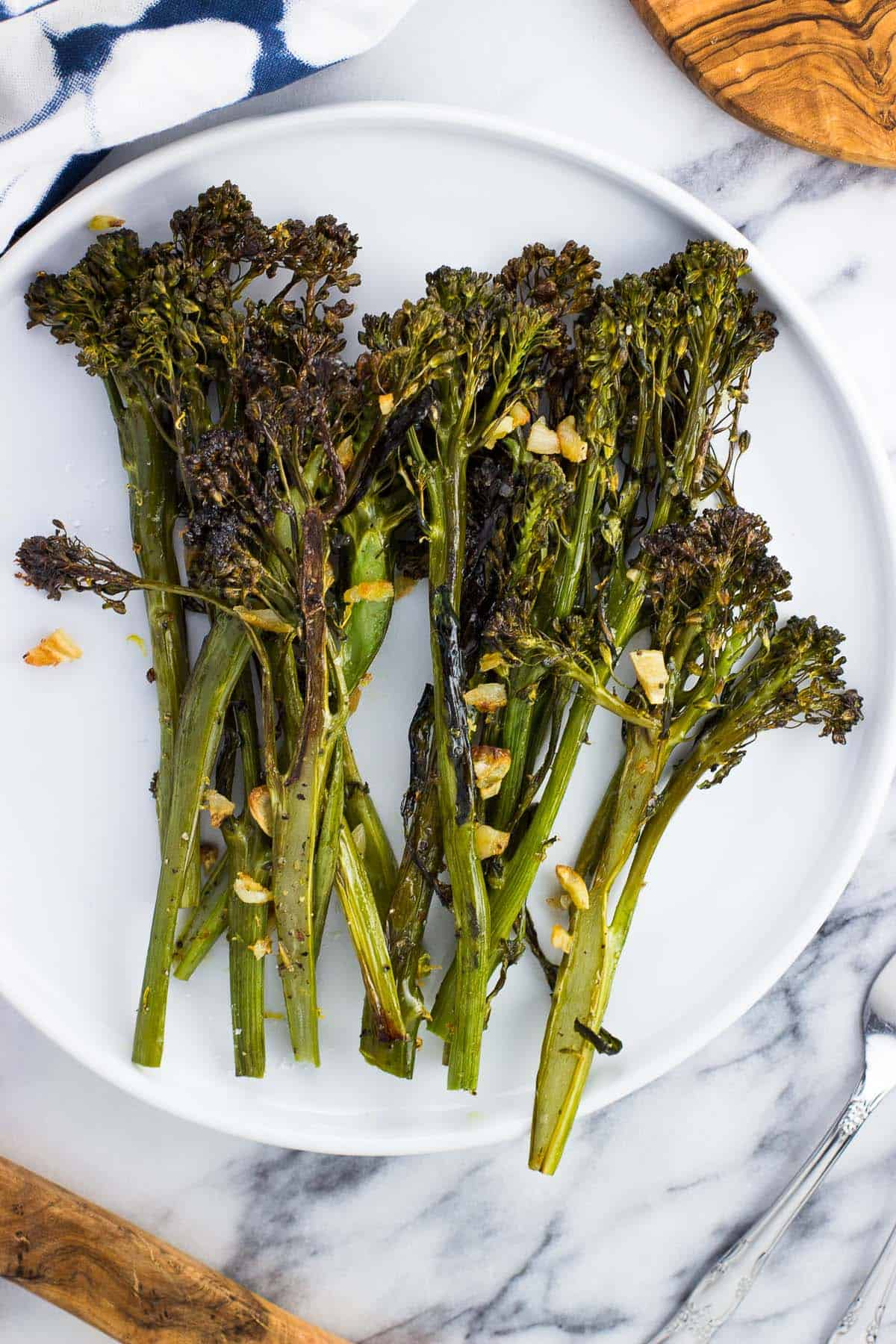 Broccolini on a plate roasted with bits of garlic.