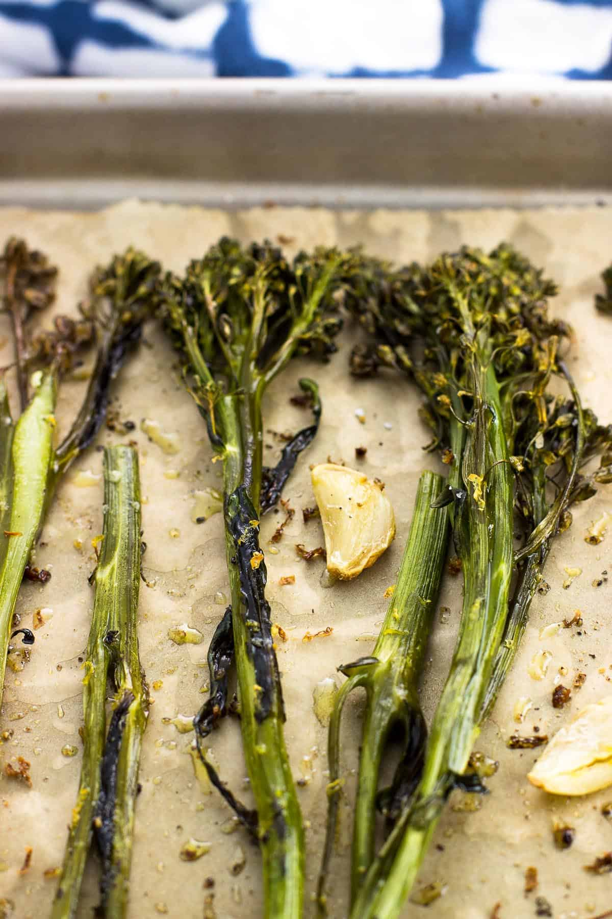 Broccolini and whole garlic cloves roasted on a parchment-lined baking sheet.