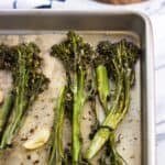 Roasted broccolini spears and garlic cloves on a parchment-lined baking sheet.