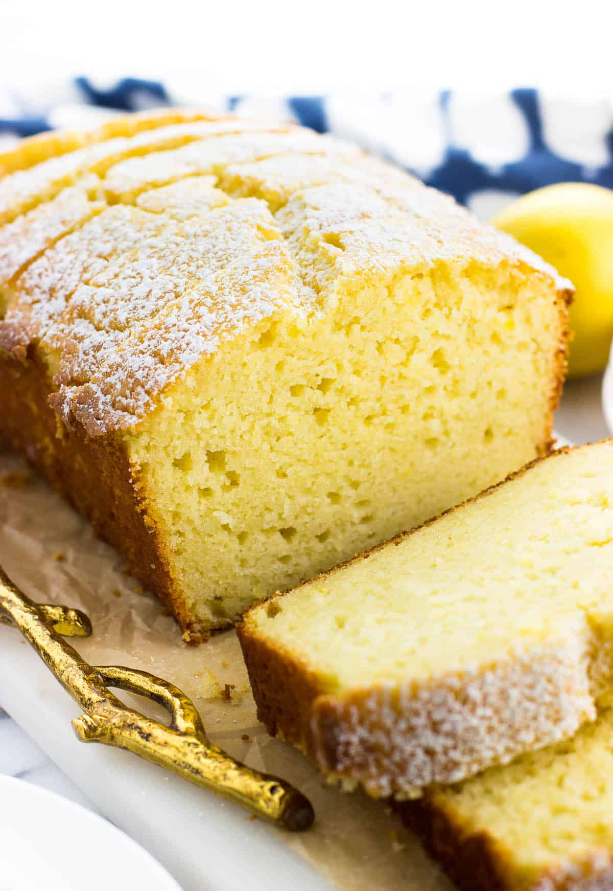 Lemon yogurt cake sliced on a tray dusted with confectioners' sugar.