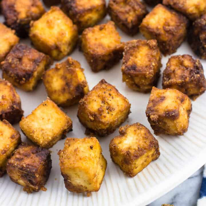 Bite-sized baked tofu cubes on a plate.