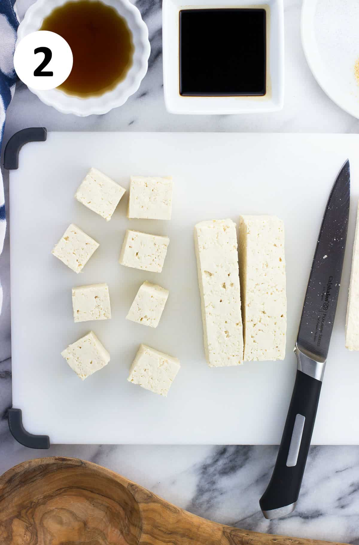 The tofu block being cut into cubes.