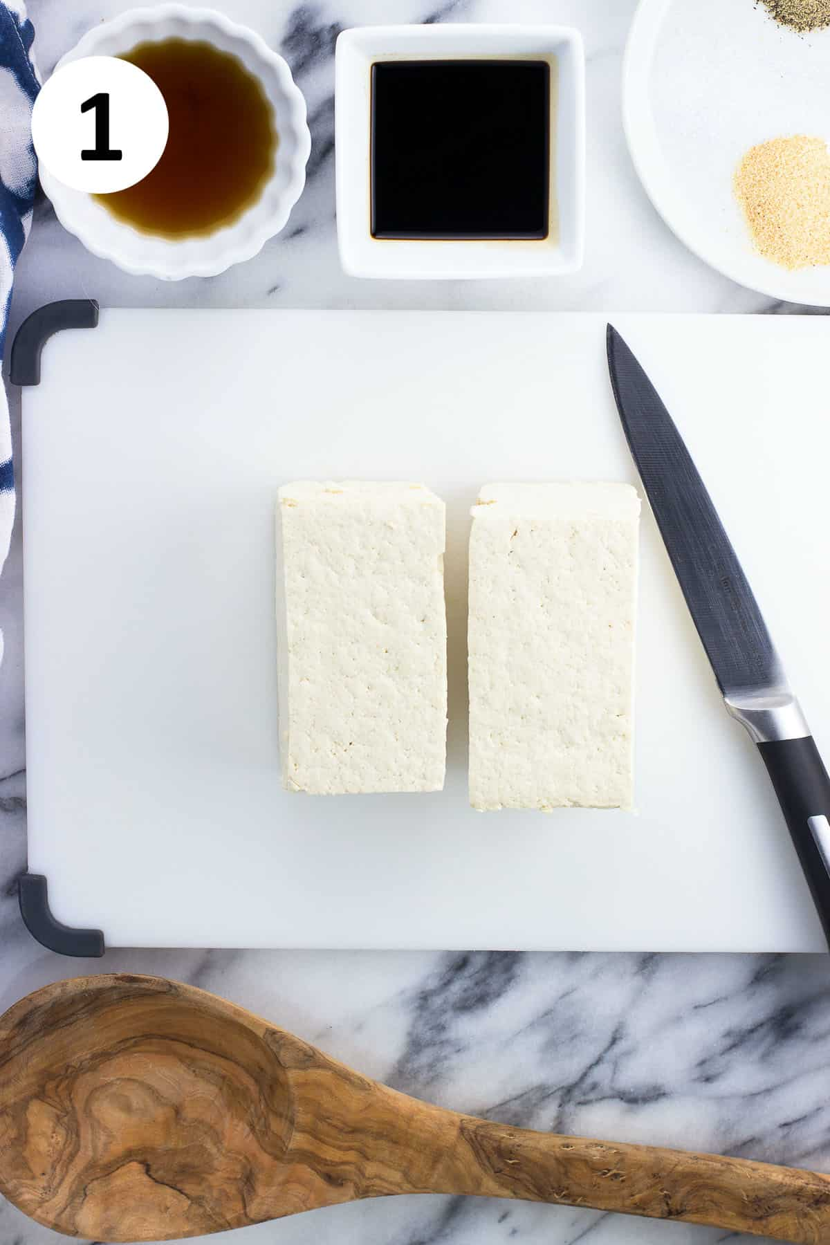 A block of pressed tofu on a board cut in half.