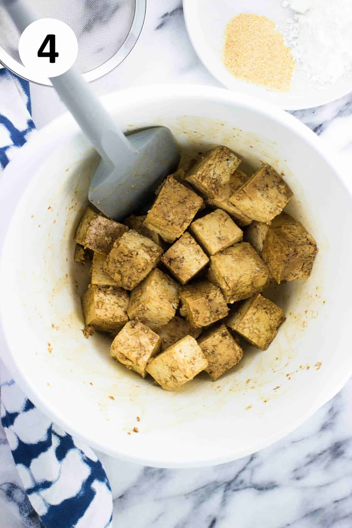 A spatula in a bowl after stirring the tofu.