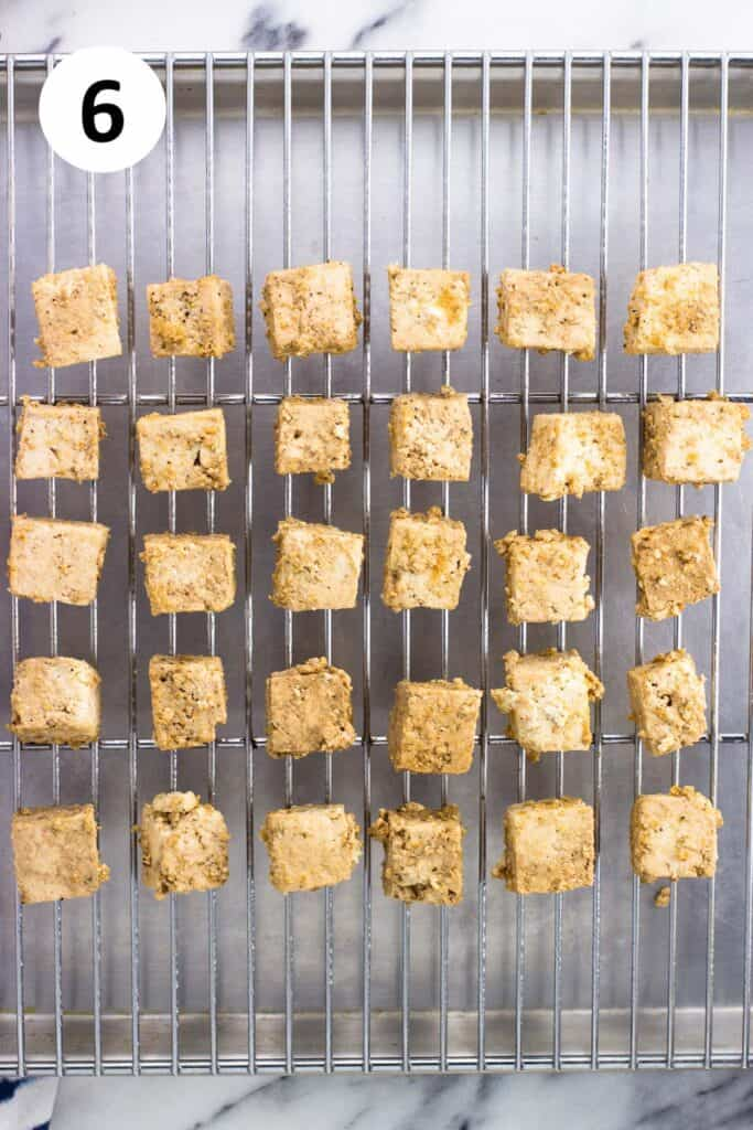 Coated tofu cubes on a wire rack set over a sheet pan.
