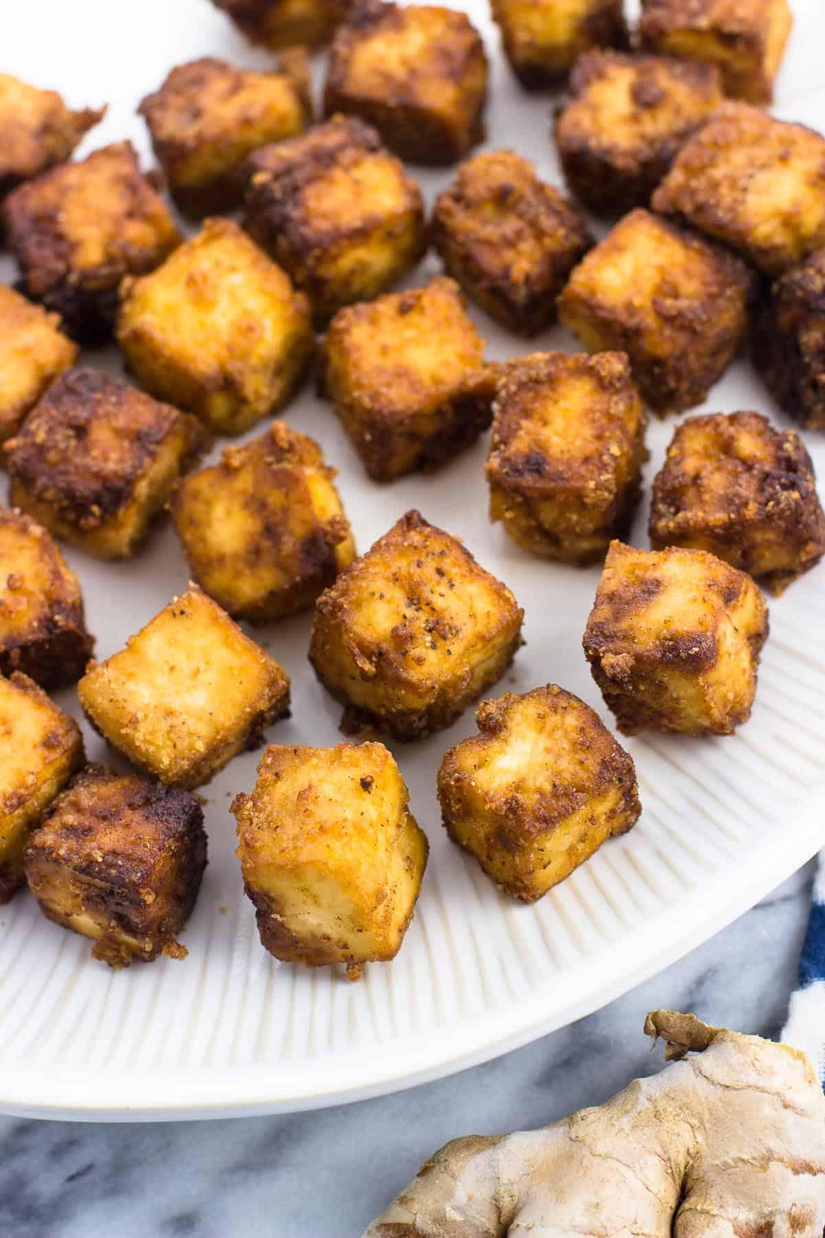 Crisp bite-sized blocks of tofu on a  plate.