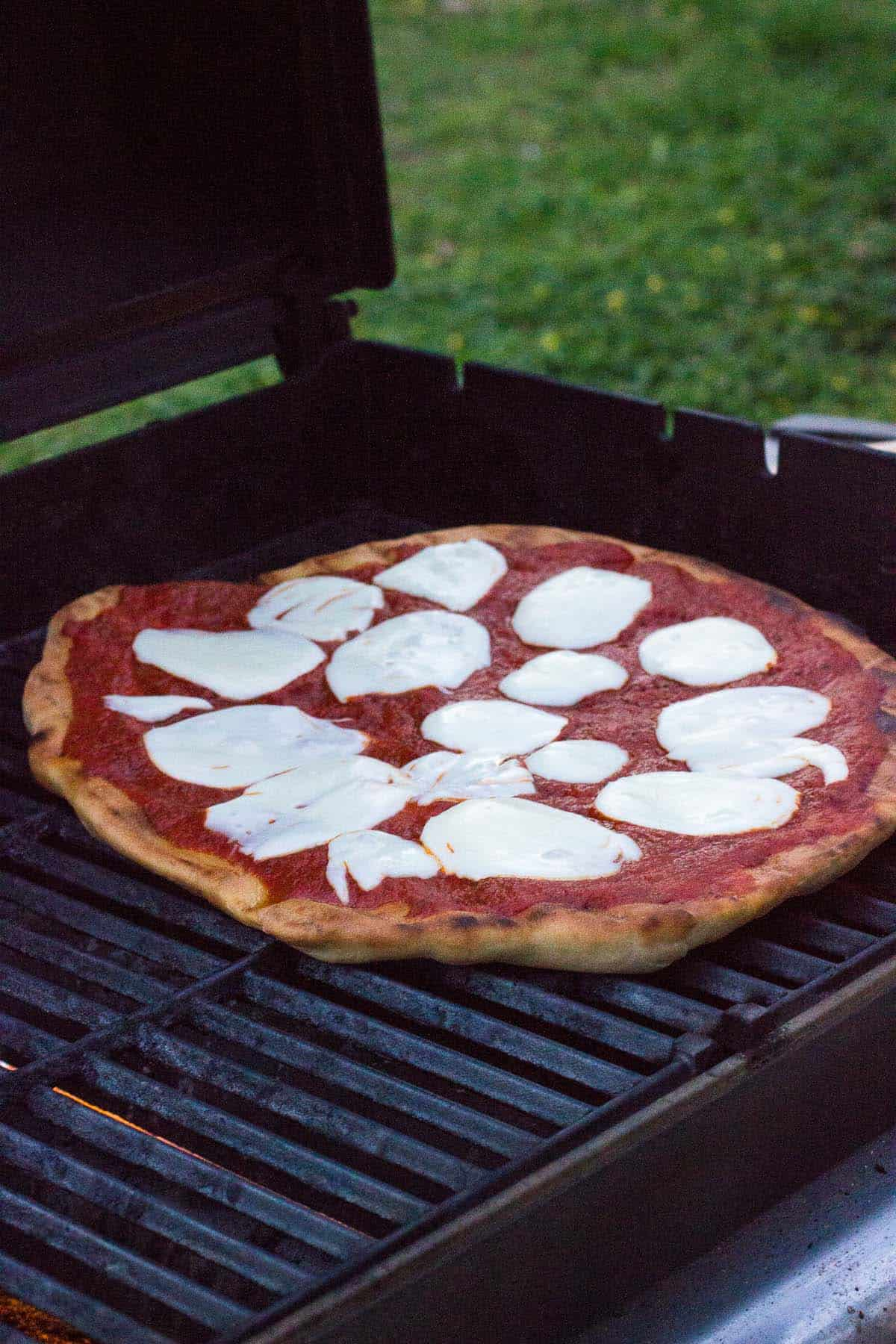 Pizza on the grill with sauce and melted mozzarella cheese.