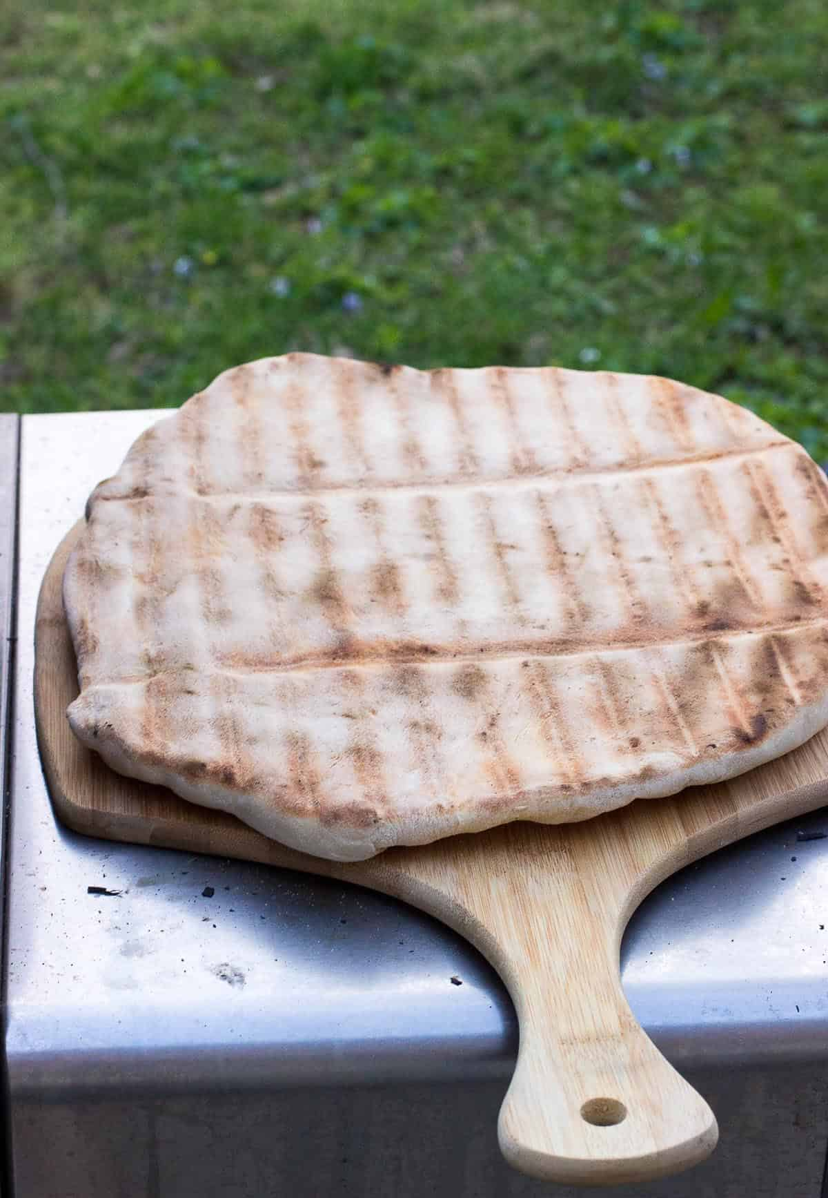Pizza crust, cooked side up, on a pizza peel.