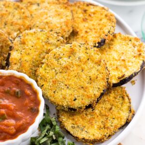 Air fried eggplant rounds on a plate with a bowl of marinara dipping sauce.