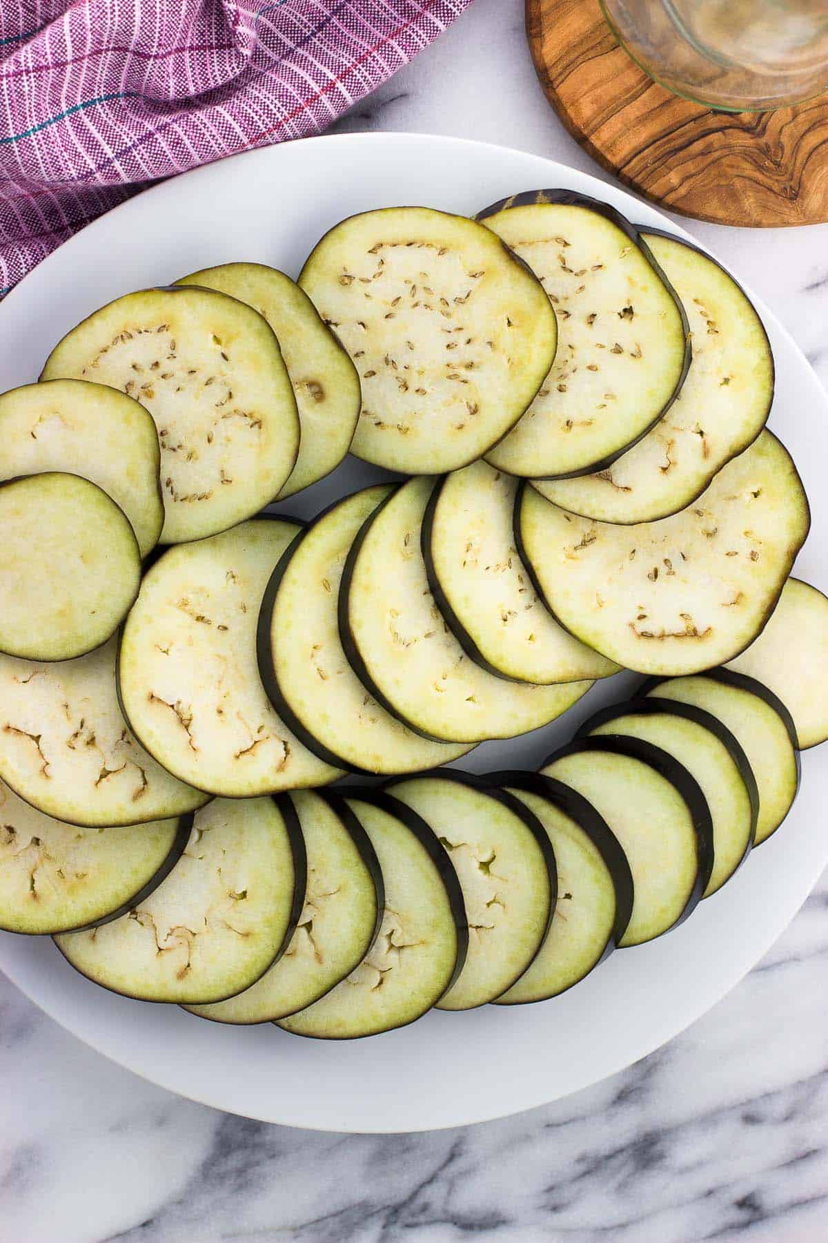 Eggplant slices laid out on a plate.