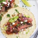 Two carne asada tacos on a plate with recipe name text overlay.