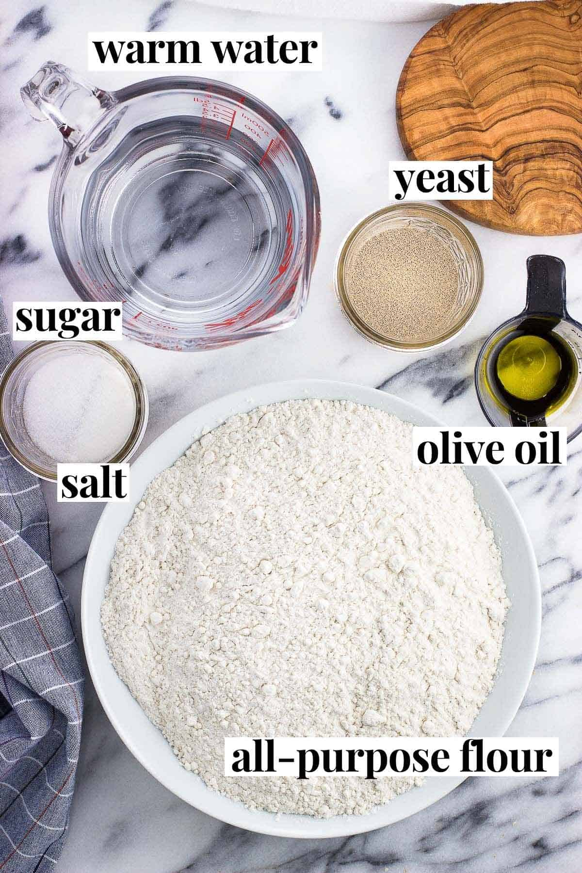 Labeled recipe ingredients in separate containers on a marble board.