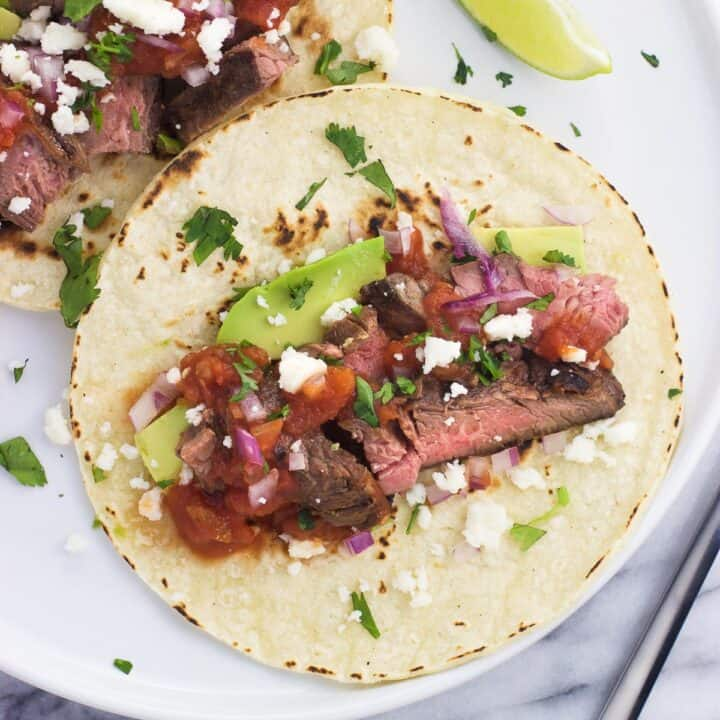 Carne asada tacos on a plate with avocado, salsa, and more toppings.