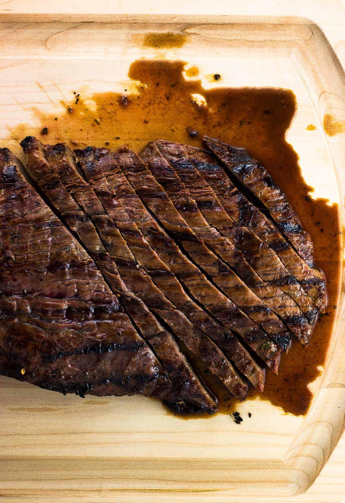Half sliced steak on a wooden cutting board.