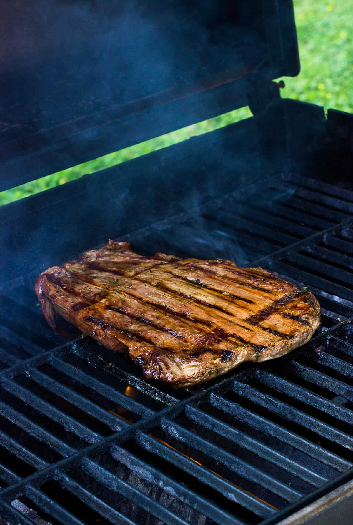 A slab of steak on the grill with smoke rising.