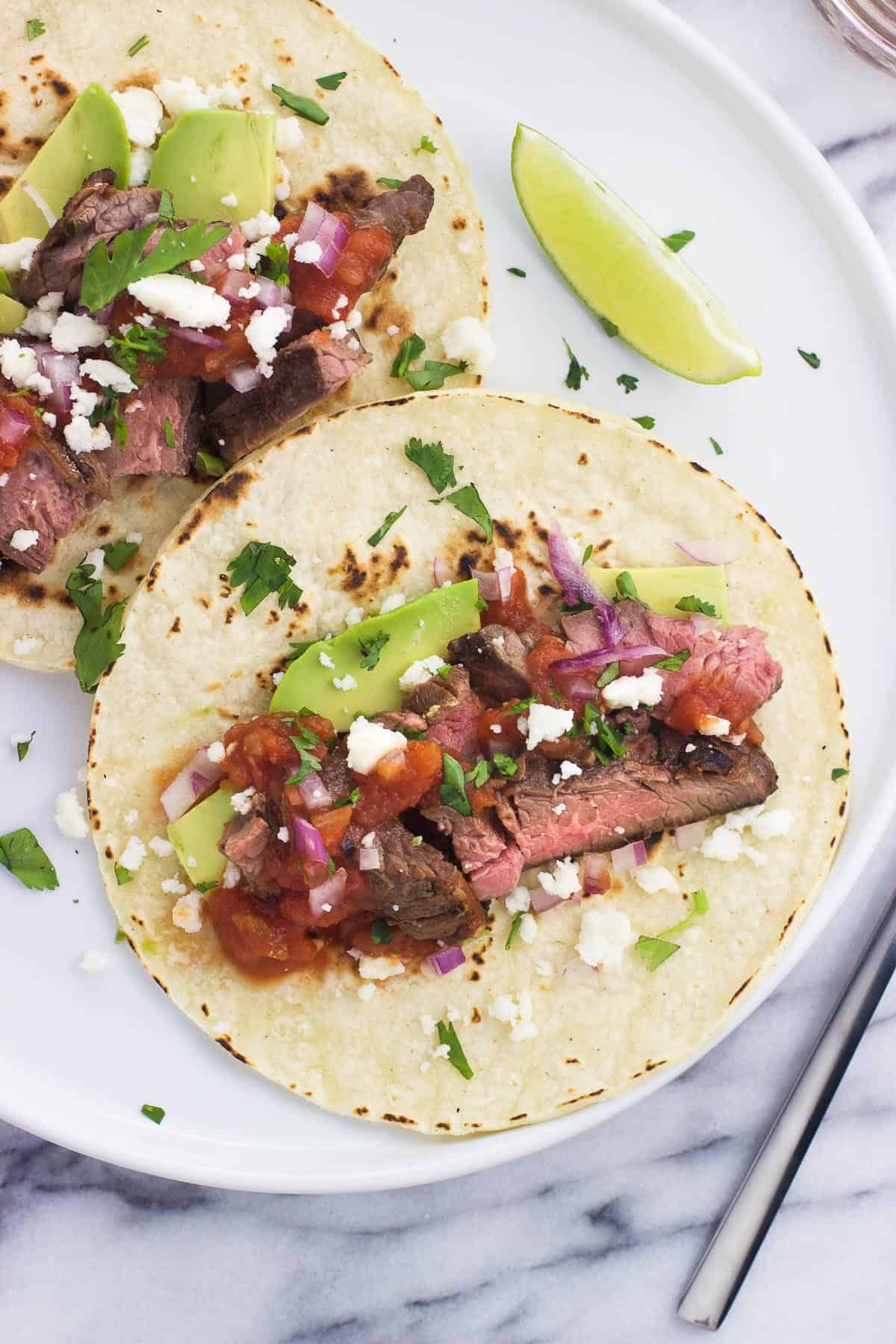 Two grilled carne asada tacos on a plate, including cotija cheese, salsa, avocado slices, and red onion.