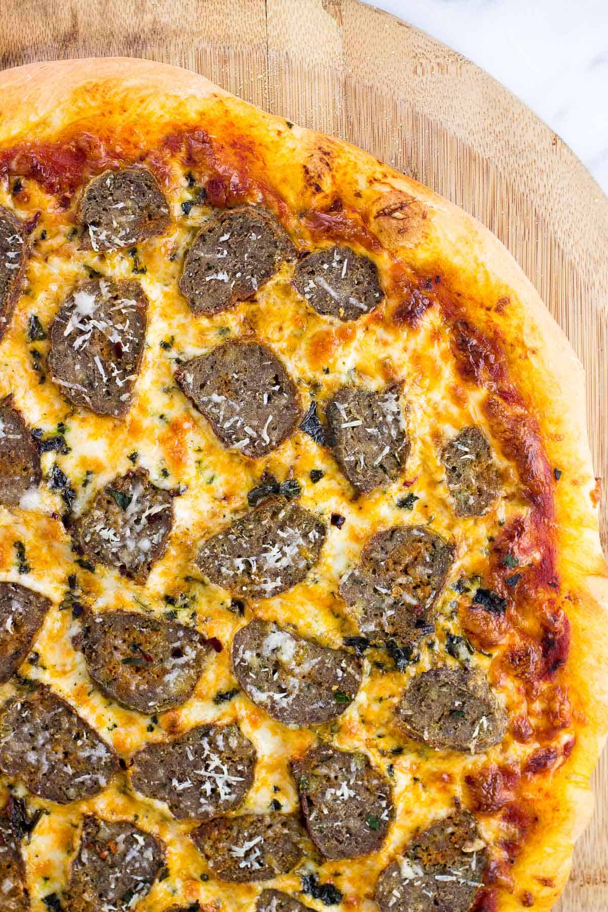 A cooked meatball pizza on a wooden peel.