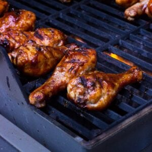 Basted chicken drumsticks on the grill.