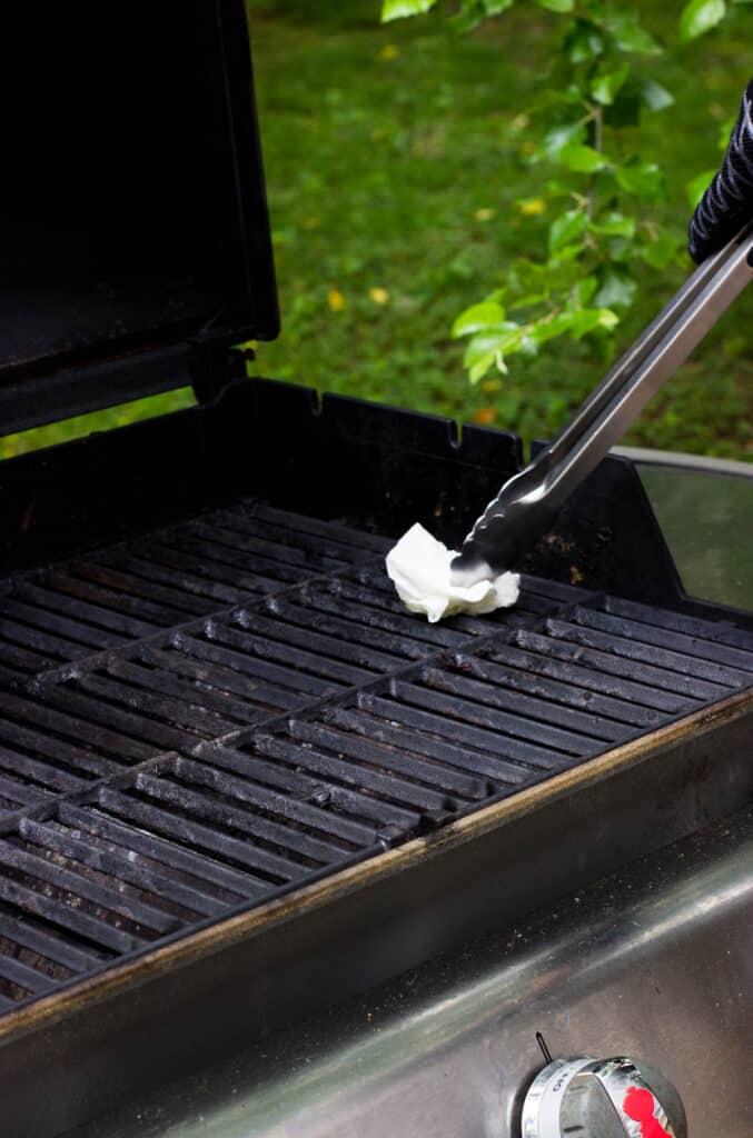An oiled paper towel being rubbed on the grill grates with tongs.