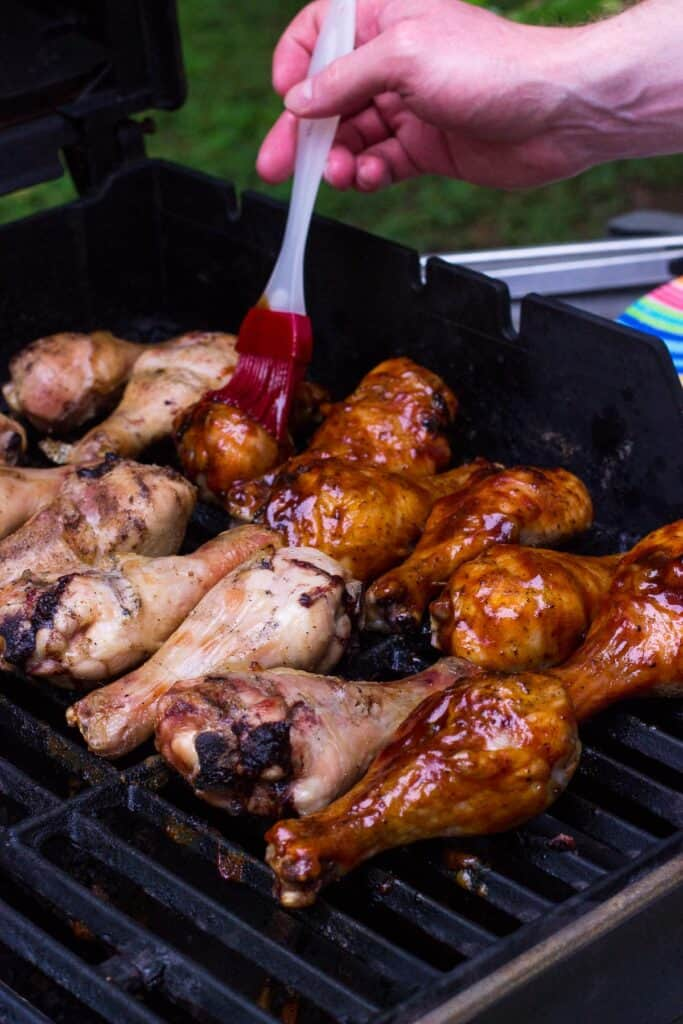 A hand brushing BBQ sauce onto chicken drumsticks on the grill.