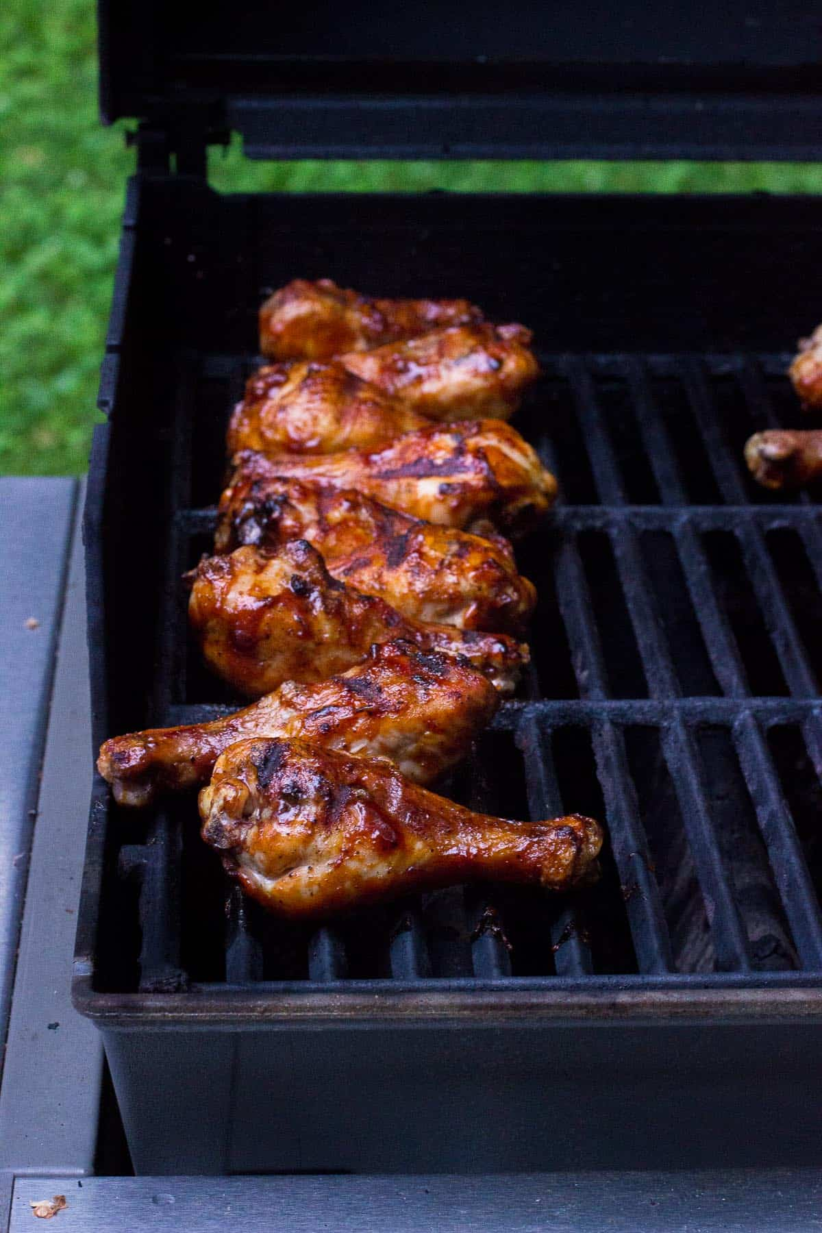 Grilled and basted chicken drumsticks lined up on the grill.