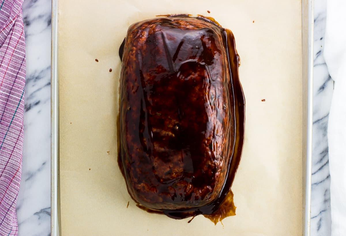 Glazed meatloaf on a sheet pan before baking.