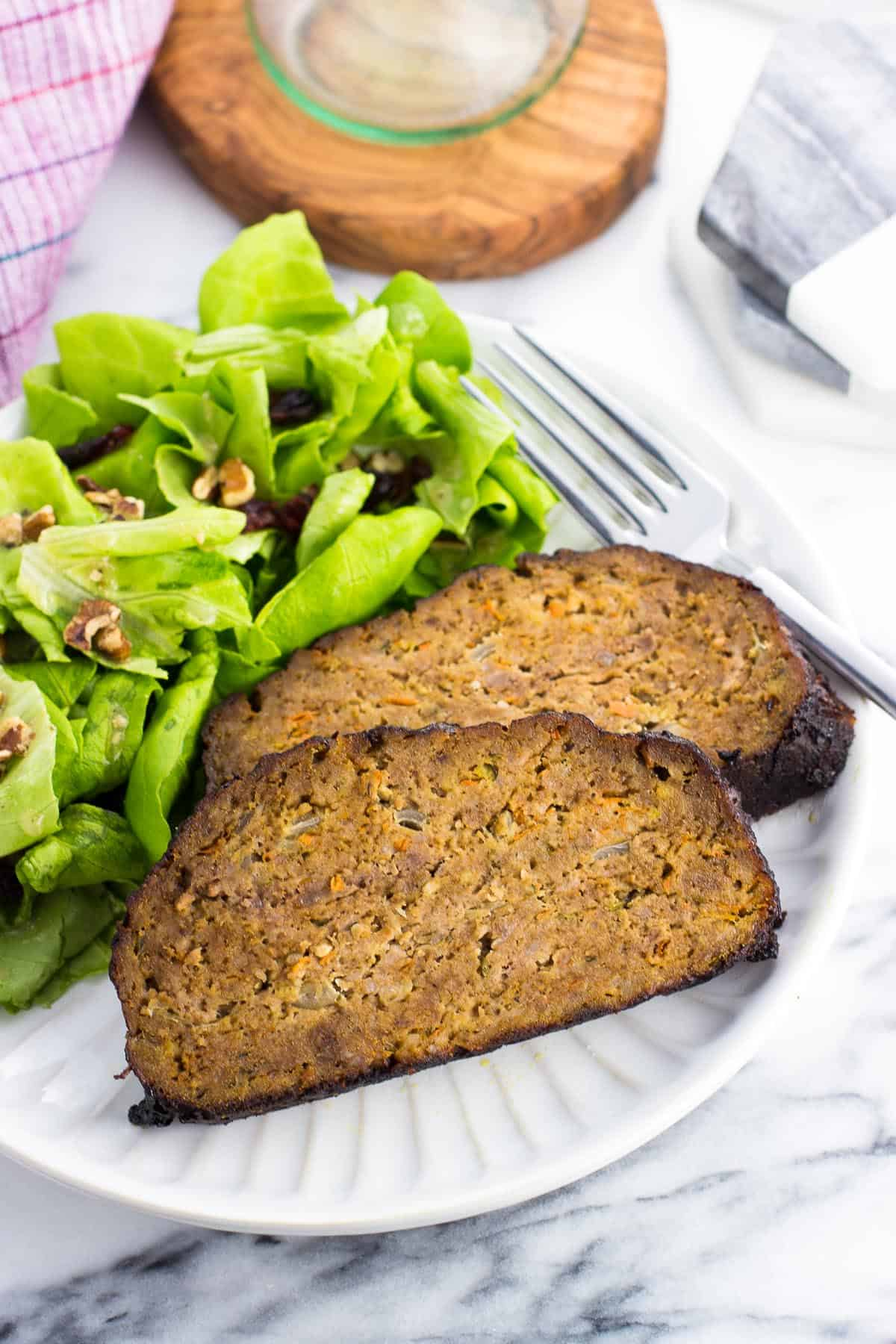 Two slices of meatloaf on a plate with a side salad.