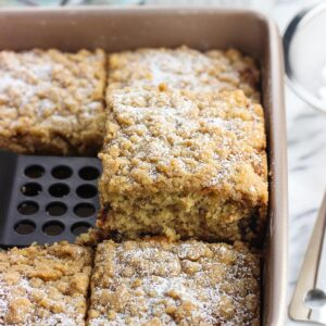A piece of crumb cake being lifted out of its baking dish by a spatula to serve.