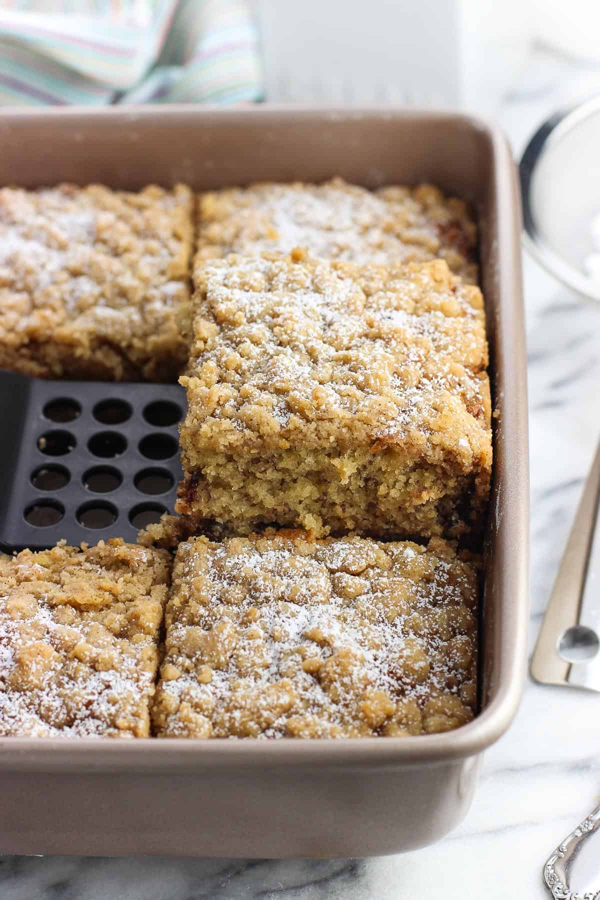 A piece of banana crumb cake being lifted out of its baking dish to serve.