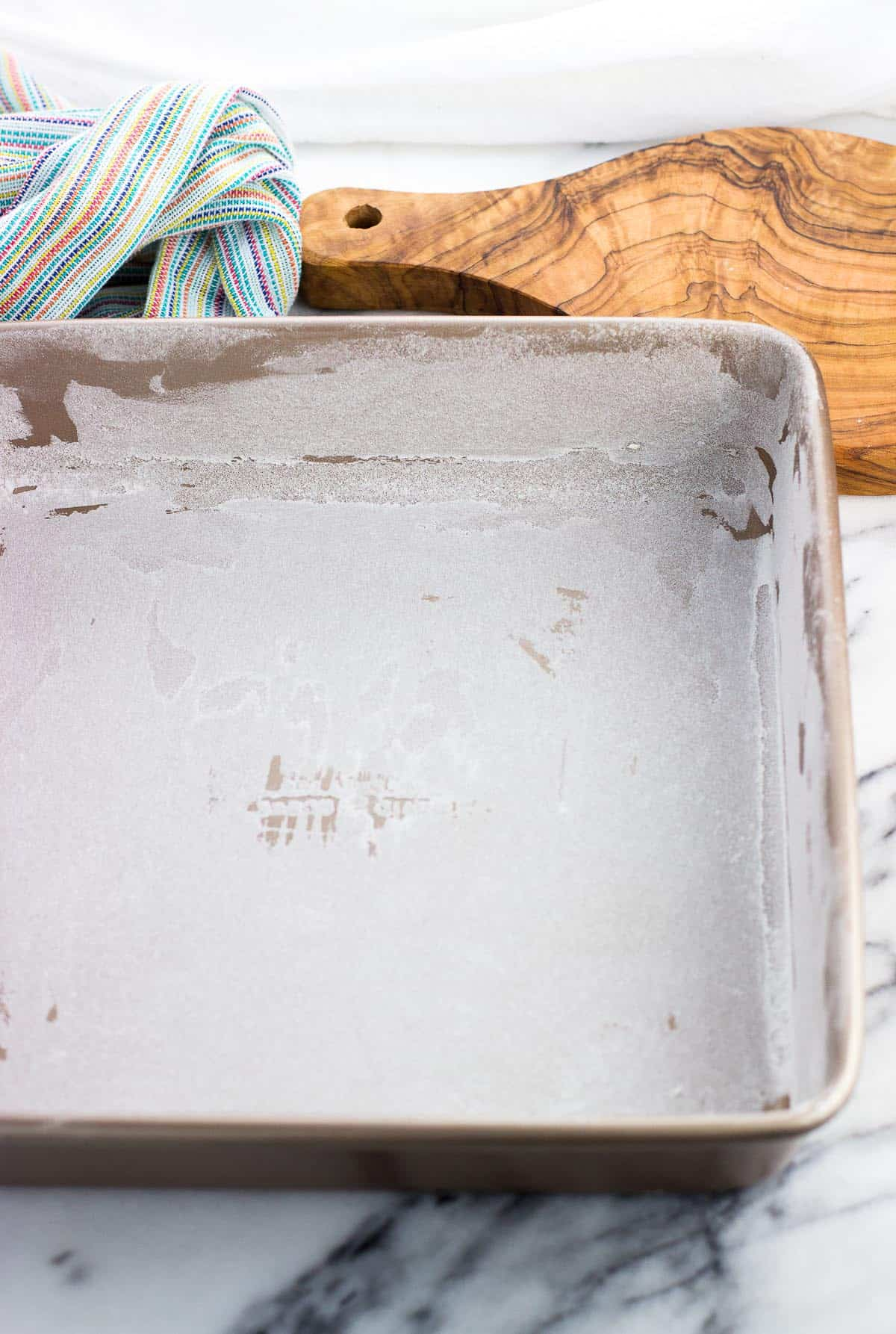A greased and floured 8-inch square pan.