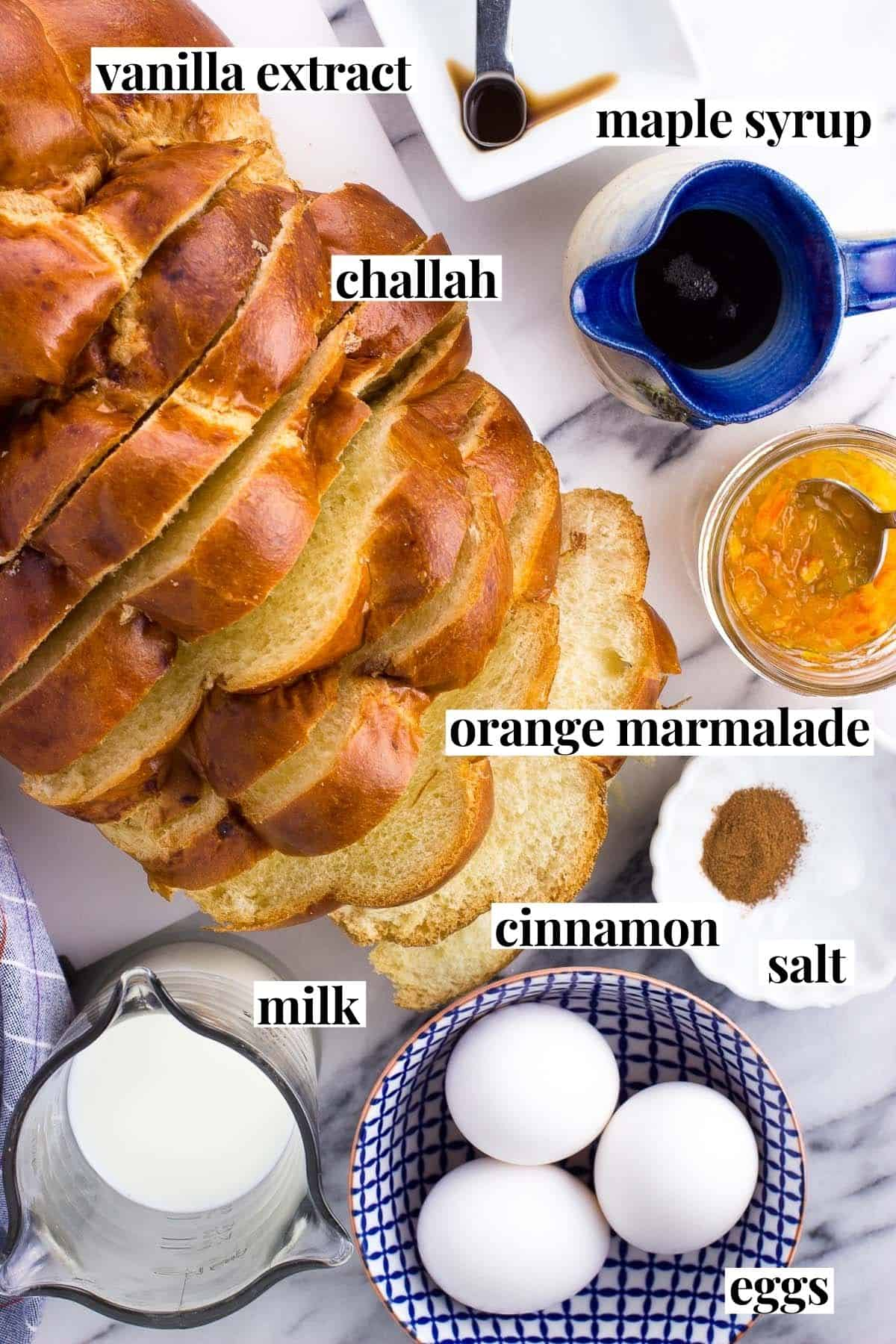 Labeled challah french toast ingredients on a marble board.