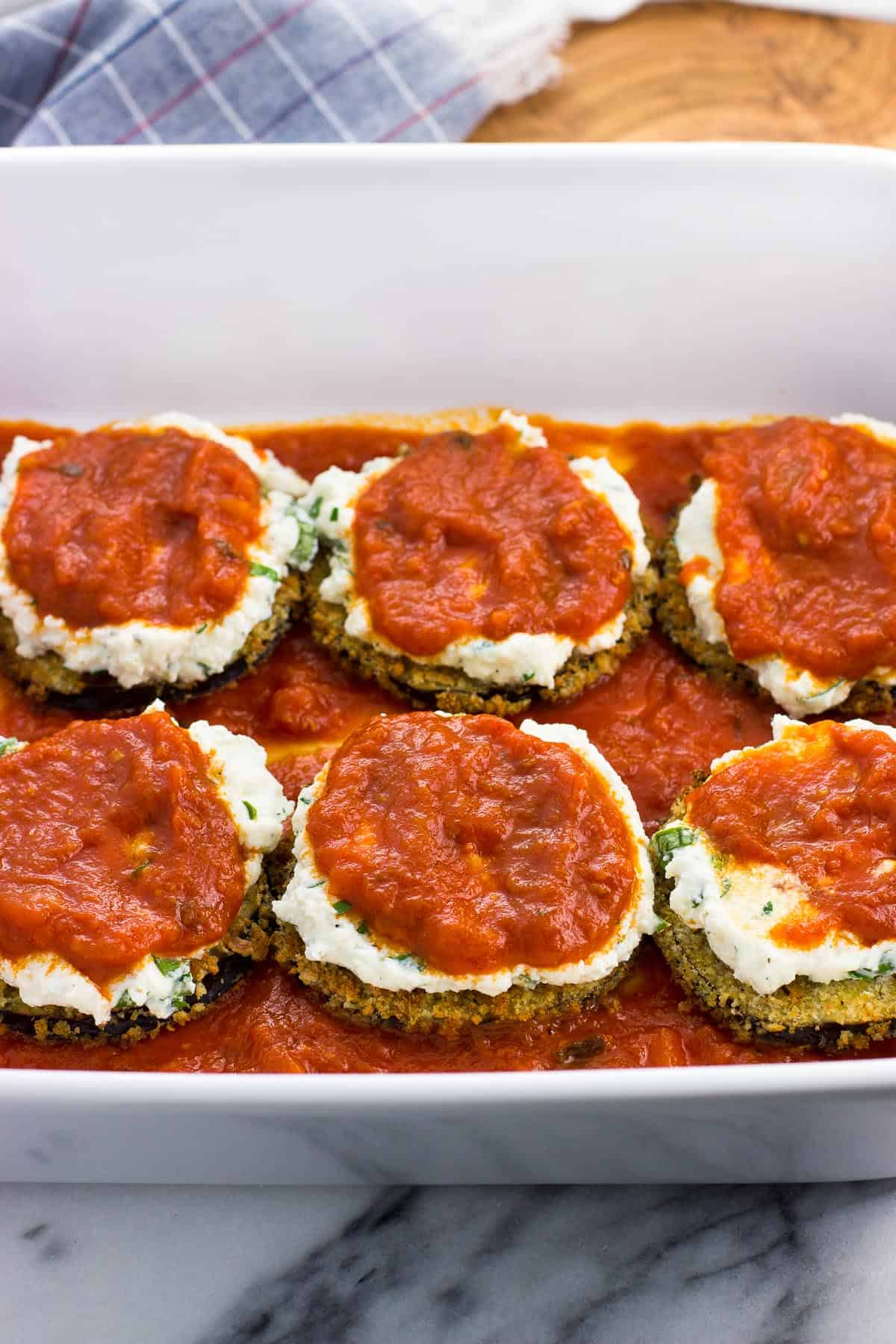 Sauce spread on top of the ricotta on the eggplant rounds.