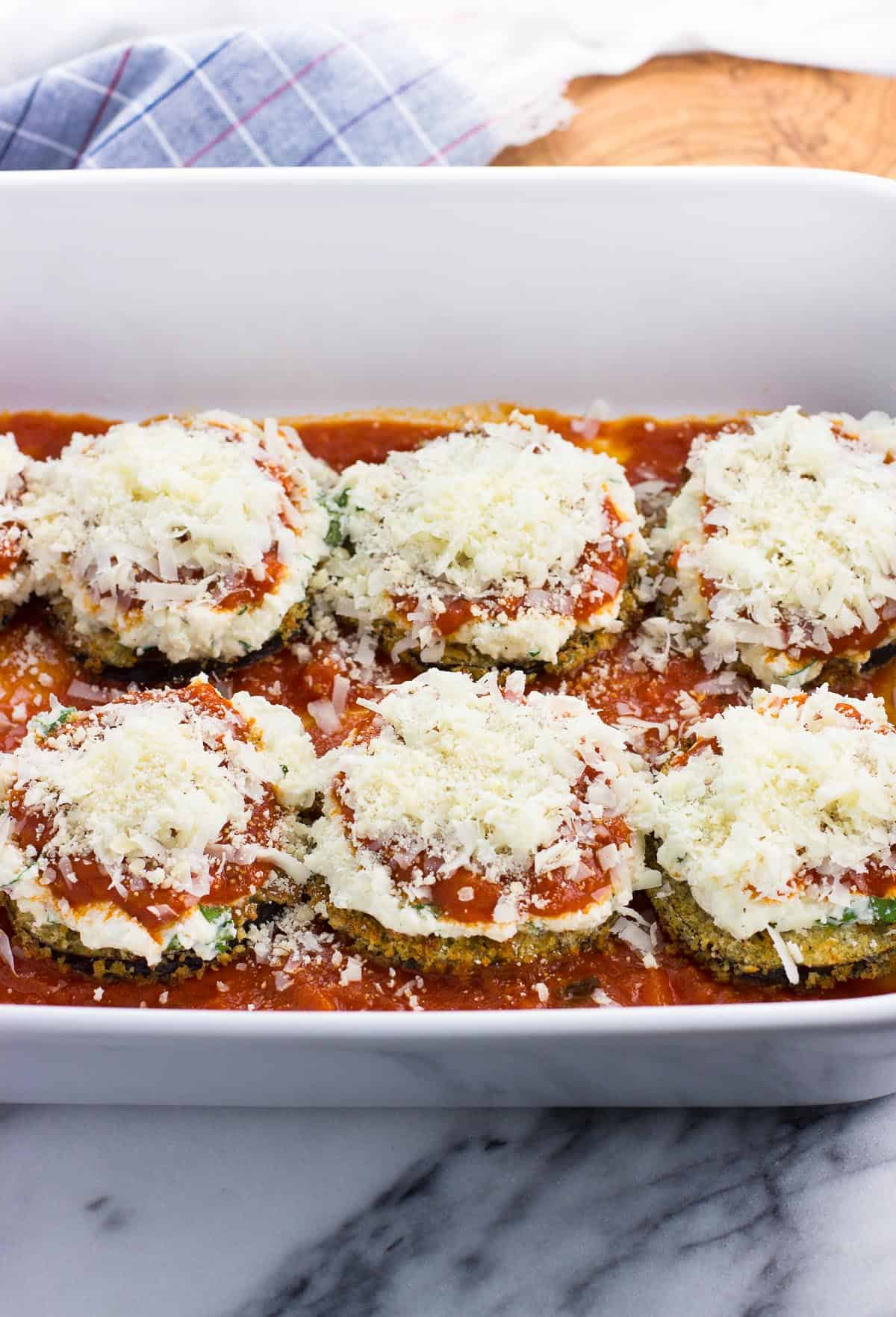 Cheese on top of the sauce and ricotta on the eggplant rounds.