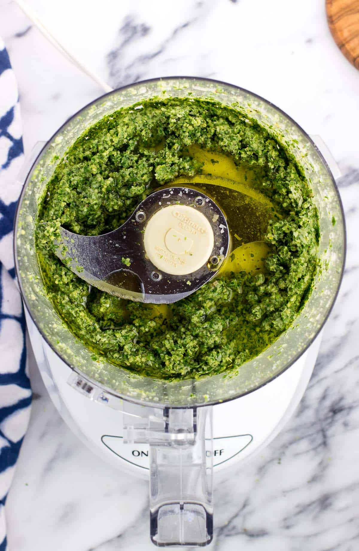 Olive oil poured into the food processor with the pesto ingredients.