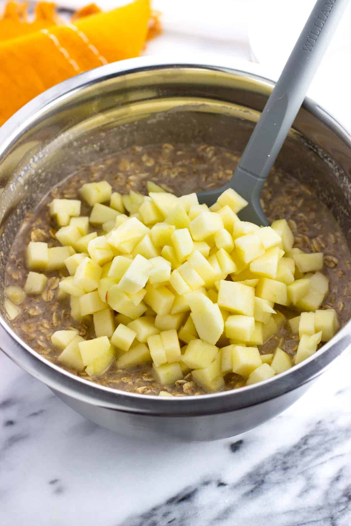 Diced apples added to the bowl with the oatmeal mixture.