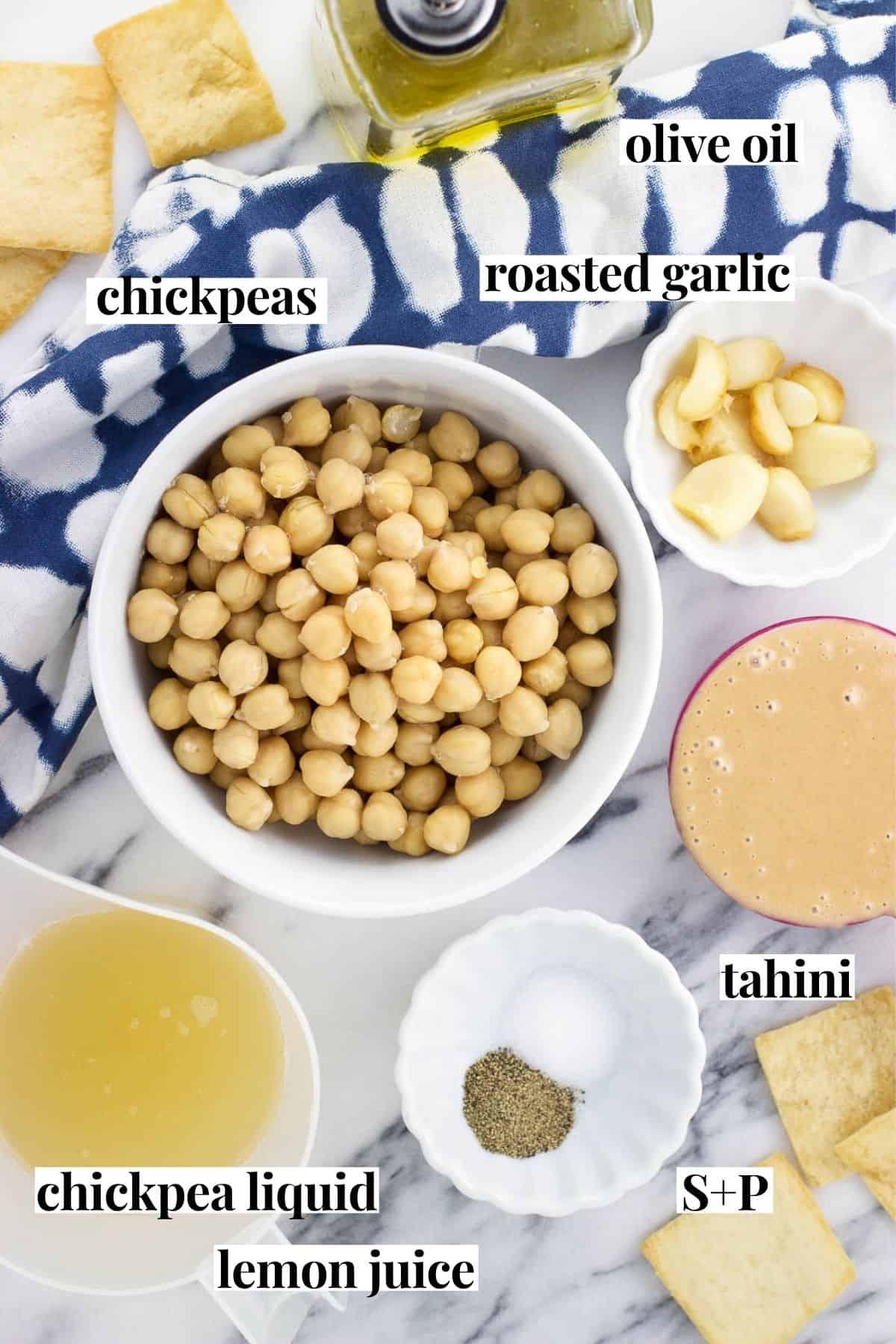 Labeled hummus ingredients in separate bowls.