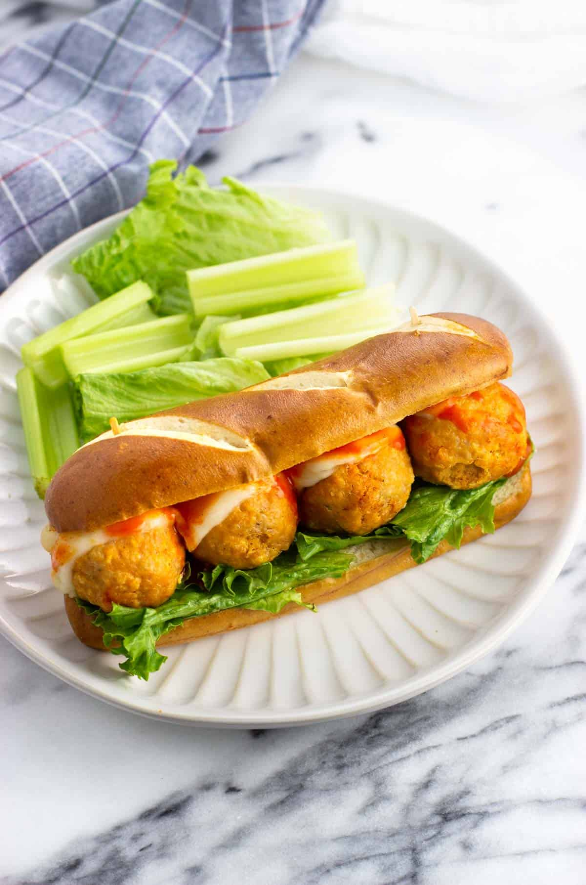 Four meatballs on a sub roll with lettuce and cheese.