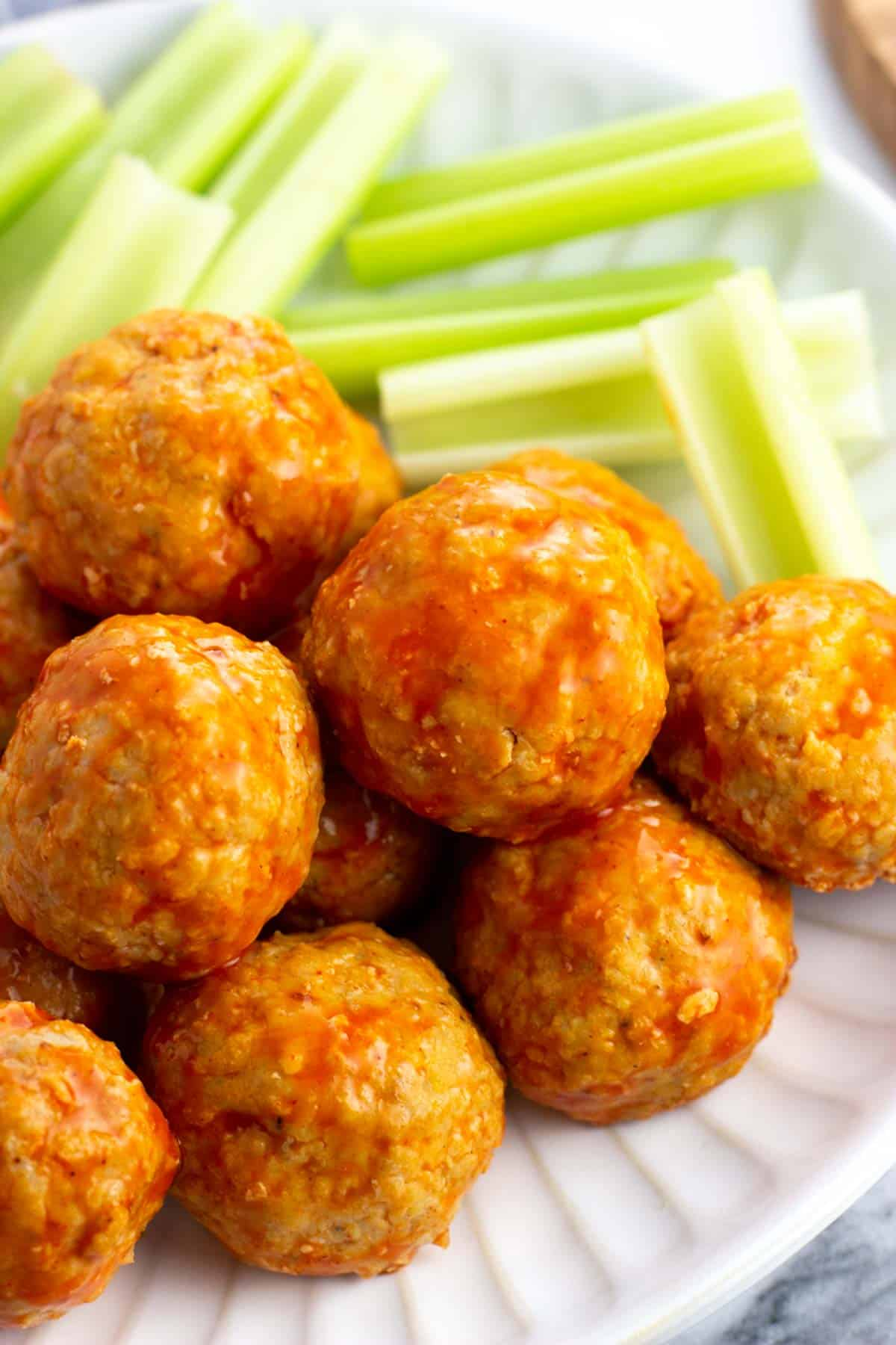 A close-up of a pile of saucy buffalo chicken meatballs.